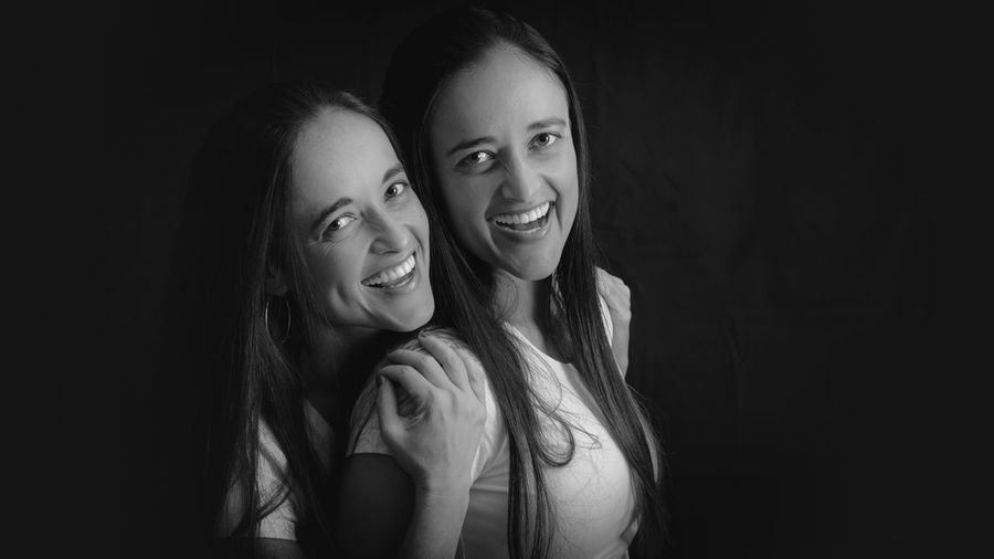Portrait of happy twin sisters against black background