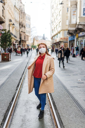 Full length of woman wearing mask standing on tramway in city