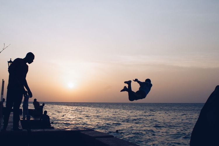 Silhouette person jumping in sea against clear sky