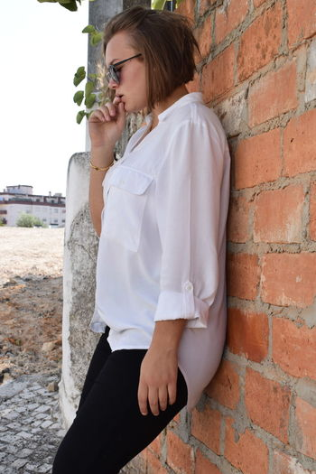 Low section of woman sitting on wall