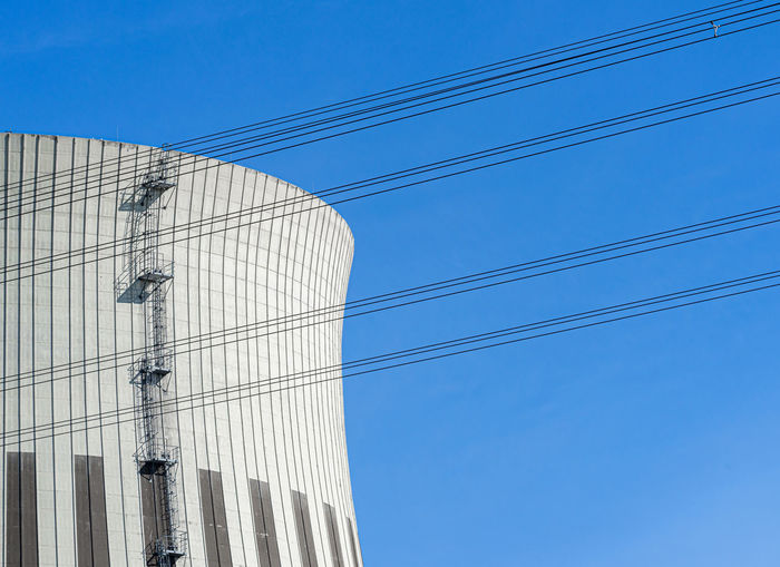 Low angle view of cables and cooling tower against clear blue sky