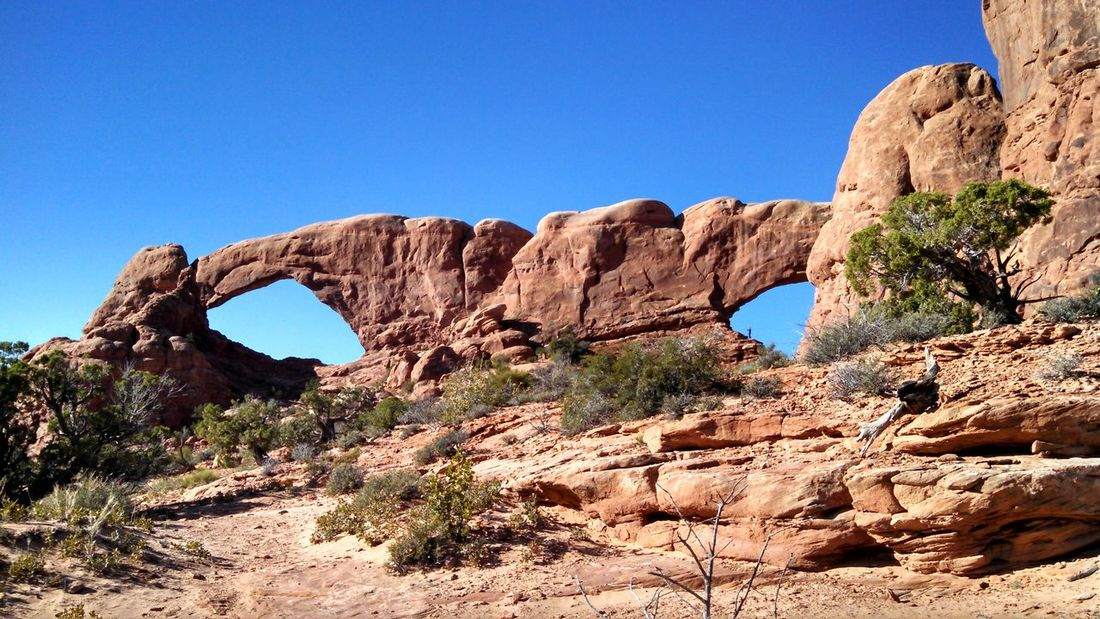 #arches #nationalpark #redrock #Utah Beauty In Nature Blue Clear Sky Cliff Copy Space Eroded Geology Landscape Low Angle View Mountain Nature Non-urban Scene Physical Geography Rock Rock - Object Rock Formation Scenics Sunlight Tranquil Scene Tranquility