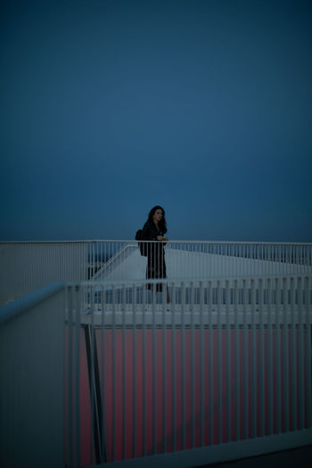 Portrait of woman standing by railing against clear sky