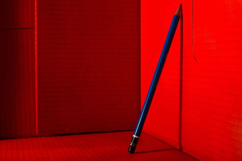 Close-Up Of Pencil By Red Wall