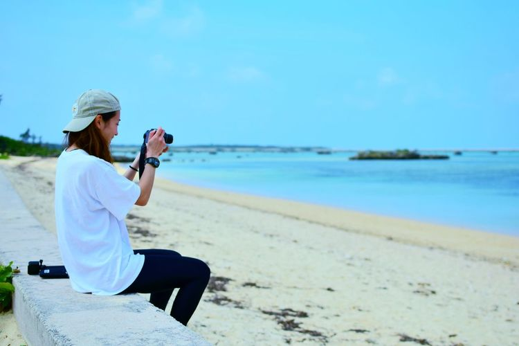Full length of woman photographing on beach