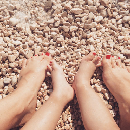 Low Section Of Mother And Daughter With Red Nail Polish At Beach