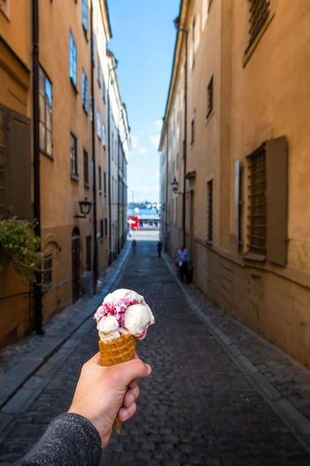 Woman holding ice cream cone on sidewalk