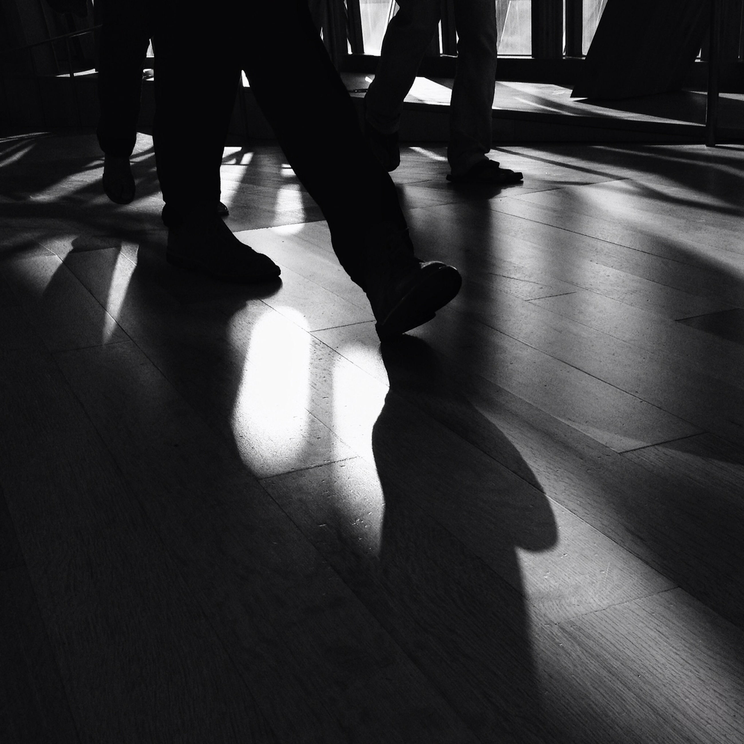 low section, indoors, person, shadow, flooring, lifestyles, standing, men, walking, human foot, tiled floor, unrecognizable person, sunlight, high angle view, leisure activity, silhouette