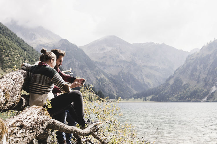 People sitting on mountain by lake against mountains