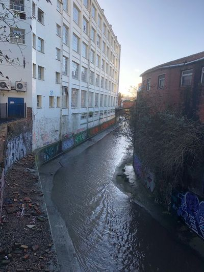 Canal amidst houses against clear sky