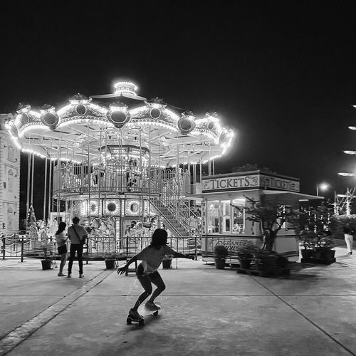 People in amusement park at night