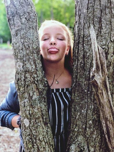 Teenage girl sticking out tongue while standing by tree trunk