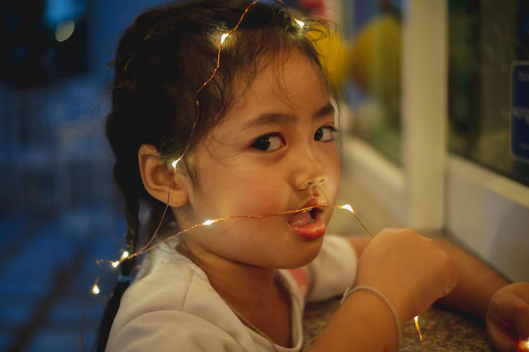 Close-up portrait of cute girl with mouth open holding illuminated lights