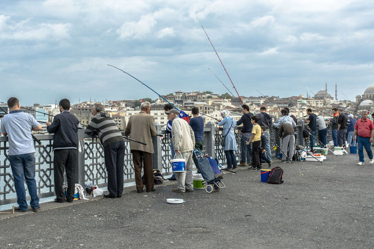 Rear View Of People Fishing At Sea