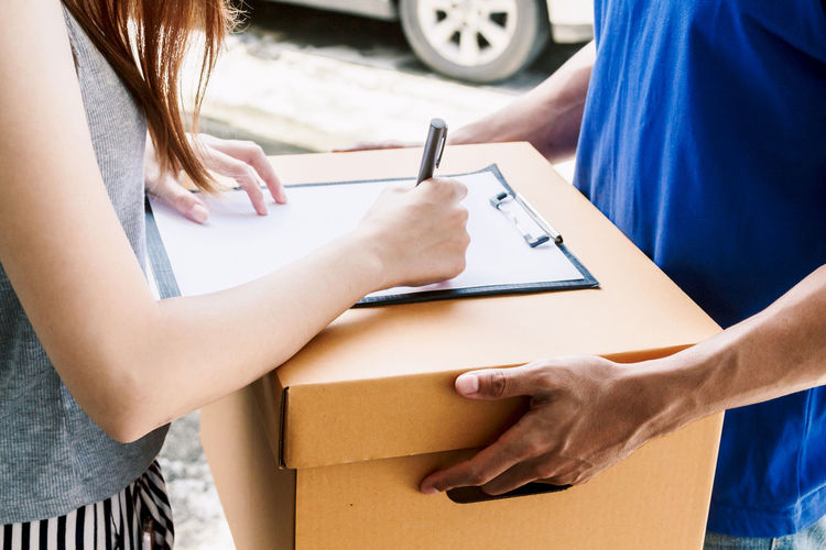 Woman putting signature in clipboard on cardboard box with delivery man Delivery Adult Box Cardboard Casual Clothing Communication Hand Holding Human Body Part Human Hand Indoors  Leisure Activity Lifestyles Men Midsection Pen People Real People Standing Two People Women Young Women