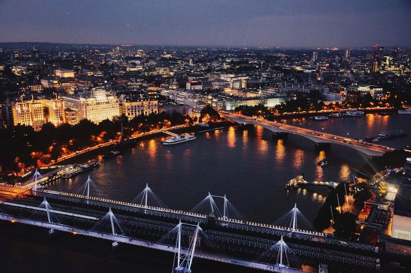 River In Illuminated City Against Sky Seen Through London Eye