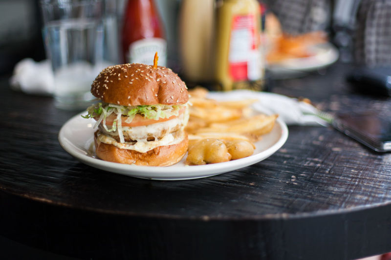 Chicken burger with french fries on a plate Burger Cafe Cheese Burger Chicken Burger Chicken Cheese Burger Close-up Fast Food Food Food And Drink French Fries Freshness Indulgence Meal Plate Ready-to-eat Restaurant Snack Still Life Table Unhealthy Eating