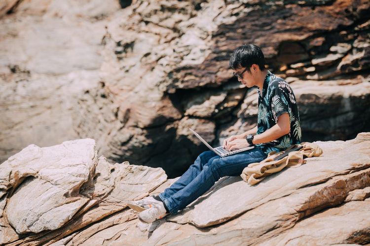 Man using laptop while sitting on rock