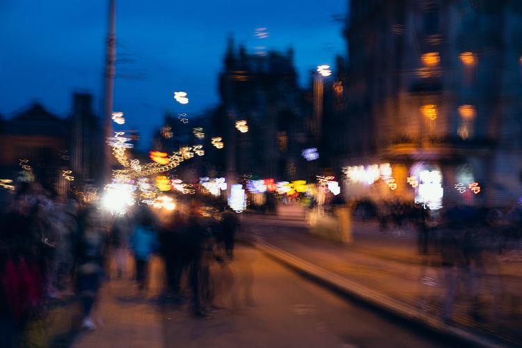 Defocused image of illuminated city street and buildings at night