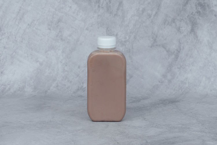 Close-up of bottle against white wall
