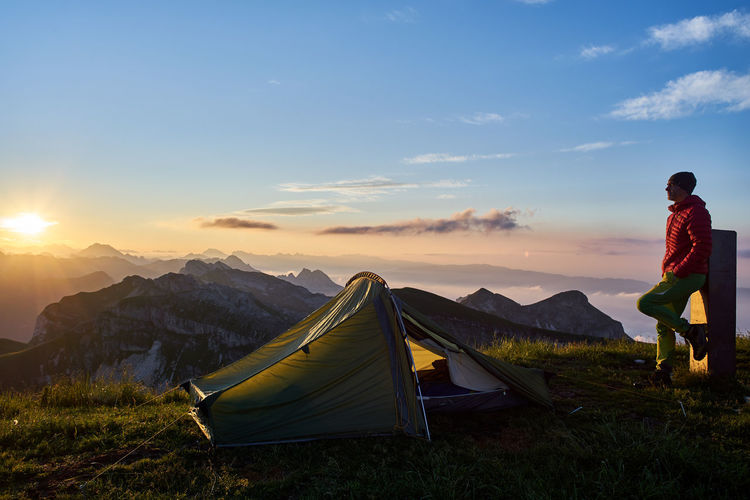 Full Length Of Man Looking At View While Camping On Field Against Sky During Sunset