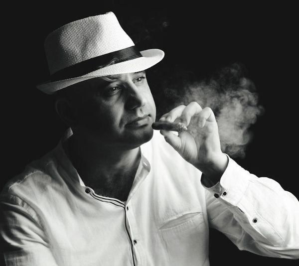 Man Smoking Cigar Against Black Background