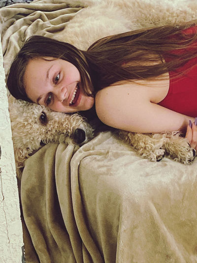 Smiling girl lying down with dog on bed at home