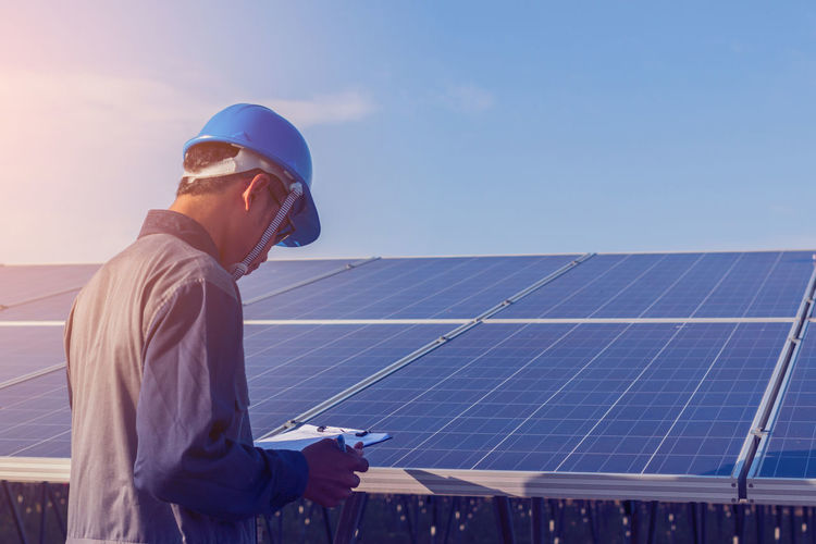 Male engineer examining solar panel against sky