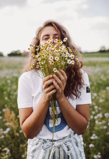 Young woman holding flower in field