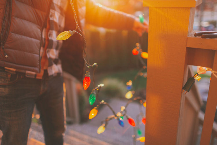 A man hanging colourful Christmas lights. Focus On Foreground One Person Decoration Hanging Christmas Lights Christmas Lights Decorating Outside Man