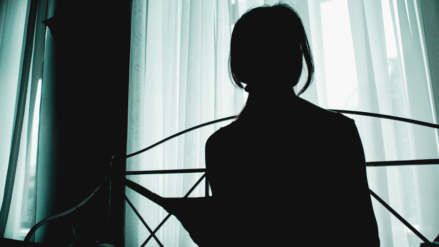 Silhouette woman standing by window