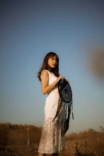 Side view portrait of woman with dreamcatcher standing against clear sky