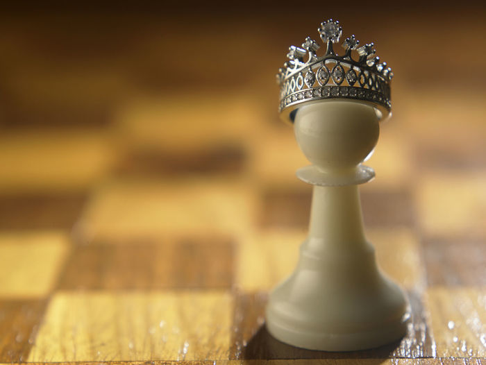 Close-Up Of Crown On Pawn At Chess Board