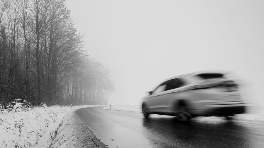 Blurred motion of car on road during winter