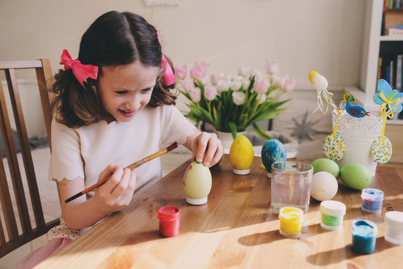 happy 7 years old kid girl painting easter eggs. Easter craft and holiday preparations at home. Colored Creativity Paint Childhood Craft Cute Day Easter Egg Elementary Age Festive Flower Girls Home Interior Indoors  Learn Lifestyles One Person People Preparation  Real People School Seasonal Spring Table