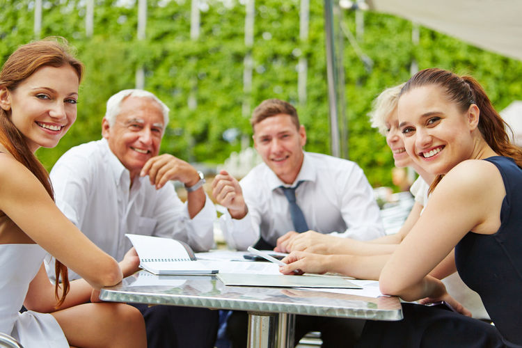 Business People Sitting At Table In Park