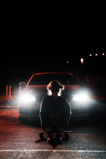 Man sitting on illuminated street at night