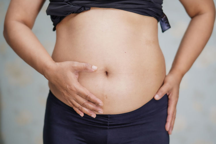 Midsection of woman standing against blurred background