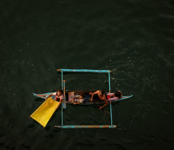 High angle view of men sitting on boat in lake