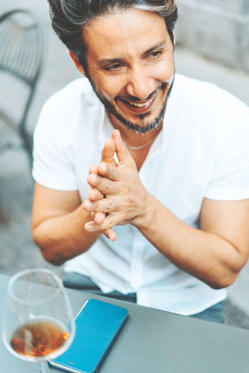 Mature man having fun on a cafe table talking with some friends Real People One Person Front View Adult Males  Smiling Mature Adult Sitting Glass Waist Up Table Looking Mature Men Holding Casual Clothing Men Wine Wineglasses Outdoors Smart Phone Drinking Glass Friendship Joy Happiness Hands Clasped