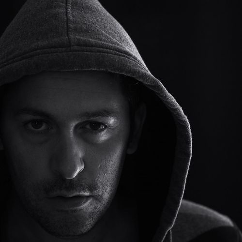 Close-up portrait of mid adult man in hooded shirt against black background