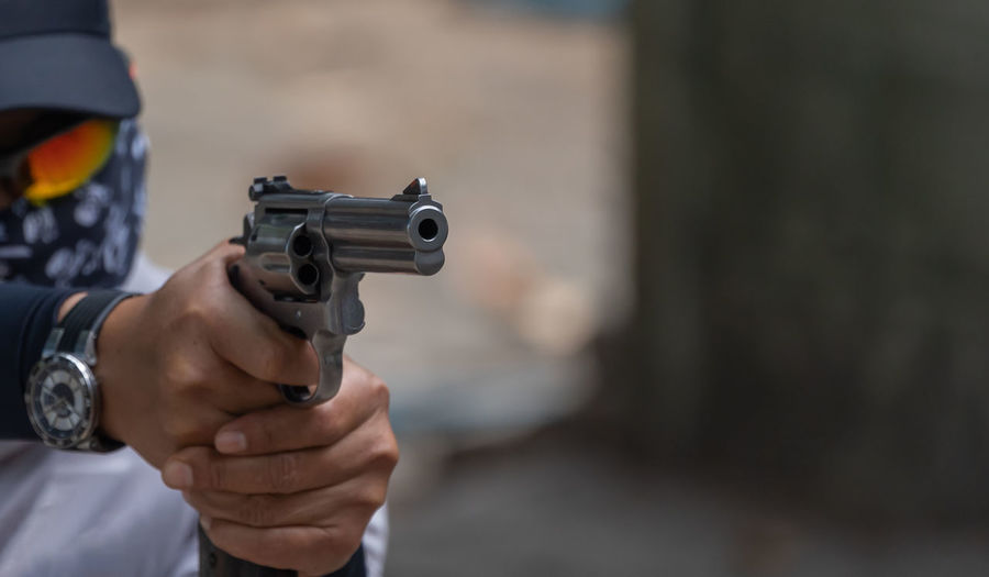 Midsection of man pointing gun outdoors
