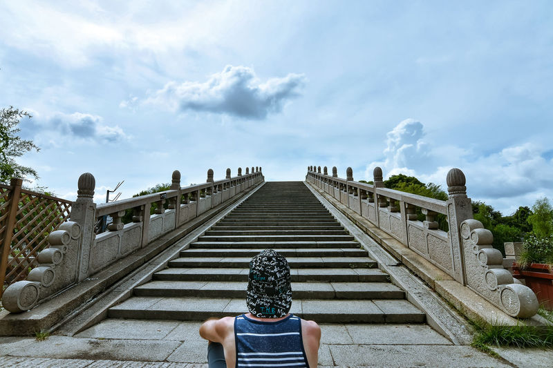 Rear view of man sitting against staircase and sky