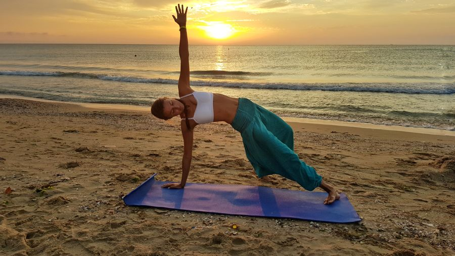 Mid Adult Woman Doing Yoga At Beach During Sunset
