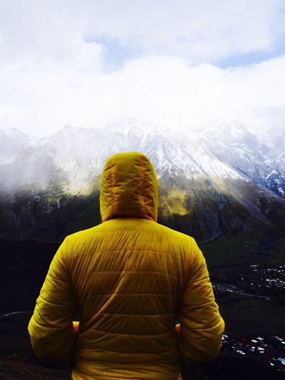 Rear View Of Person In Yellow Hooded Jacket Standing Against Snowcapped Mountains