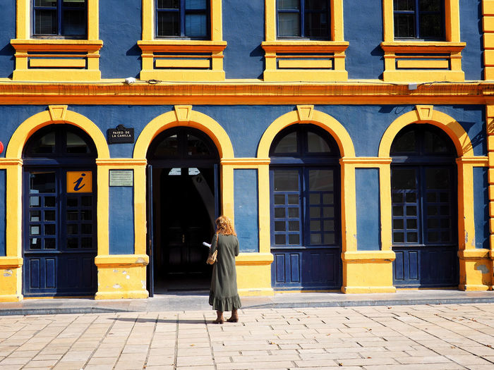 Rear view of woman walking on footpath against building