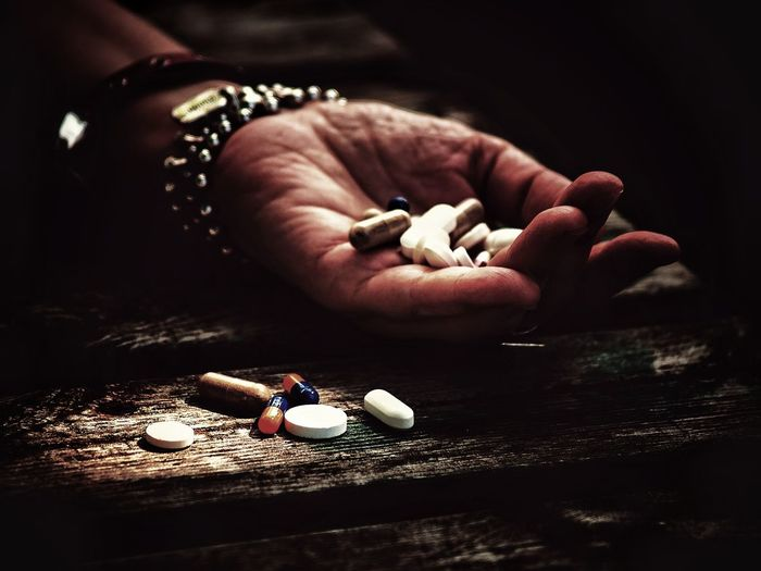 Cropped hand of woman holding pills outdoors