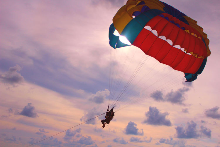 View Of Person Parasailing Against Cloudy Sky At Dusk
