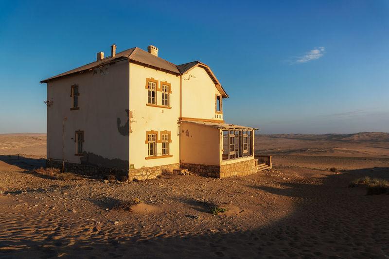 House on beach by building against sky