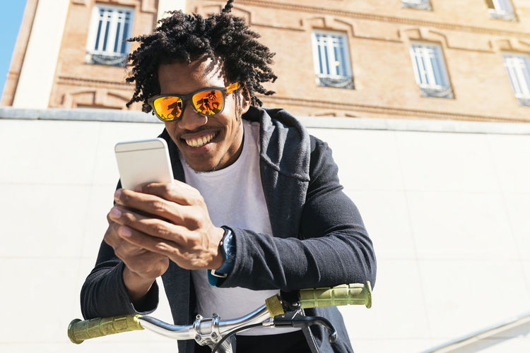 Low angle view of smiling young man wearing sunglasses using mobile phone against building